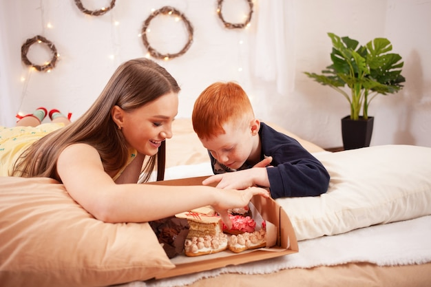 Брат и сестра едят пирожные в постели, веселятся