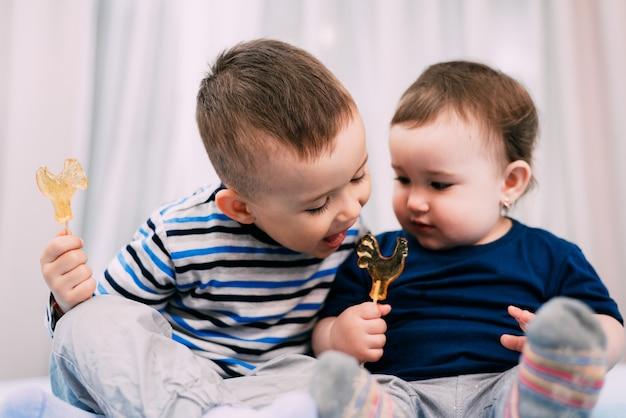 Брат и сестра едят леденцы в виде петуха, сестра дарит вкус своего леденца на палочке