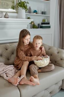 형제와 자매는 소파에 집에 앉아 팝콘을 먹고