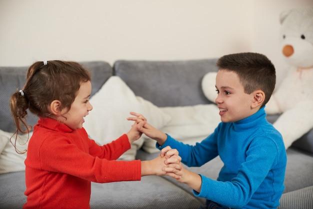 형제와 자매는 함께 박수를 치는 동안 손을 잡습니다. 어린 시절.