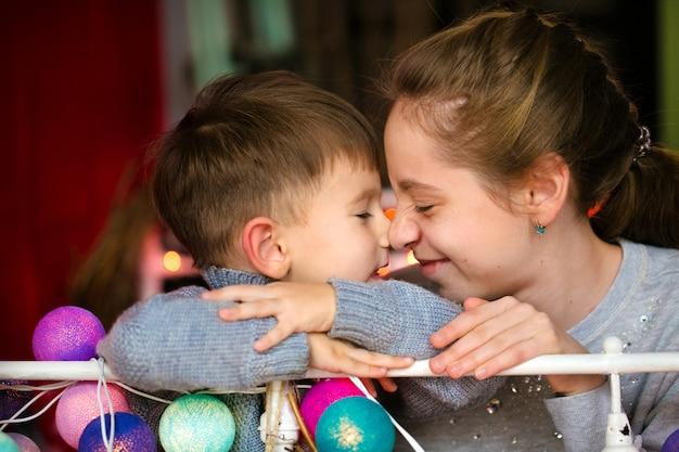 Брат и сестра, обнимаются, веселятся, в доме, украшенном на новый год