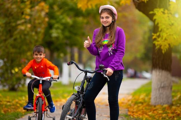 Брат и сестра в парке. девушка с велосипедом показывает, что ей это нравится.
