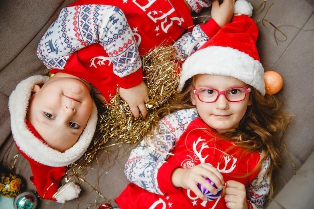 빨간 산타 모자를 쓴 형제와 자매는 서로 머리를 맞대고 누워 있습니다. 안경 소녀입니다. 상단에서보기