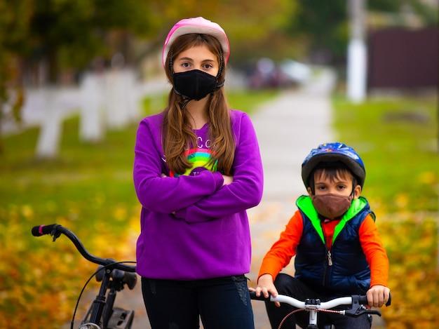 Брат и сестра в осеннем парке катаются на велосипедах в защитных масках. в стене размытый осенний парк. концепция пандемии и вируса.