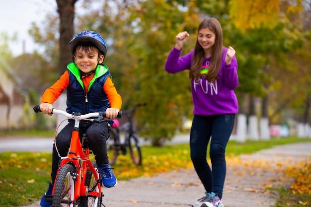 Брат и сестра в парке. мальчик учится ездить на велосипеде в одиночку. сестра в стене радуется его успеху.