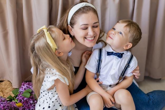 兄と妹は彼らの母親にキスします笑顔の女性は幸せな家族の2人の子供の概念を受け入れます