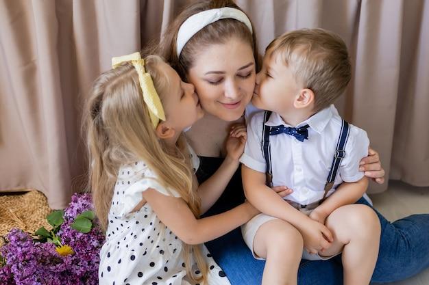 兄と妹は母親にキスします笑顔の女性は幸せな家族の2人の子供の概念を受け入れます