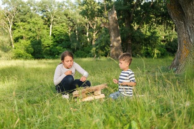 Брат и сестра учатся разводить костер на летнем поле на открытом воздухе. семейный поход. счастливая семья. фото высокого качества