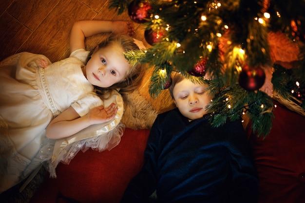 兄と妹は居心地の良いクリスマスのインテリアのクリスマスツリーの近くのカーペットの上に横たわっています