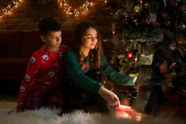 兄と妹は居心地の良い夜にお祝いのクリスマスツリーのそばに床に座ってプレゼントを開きます...