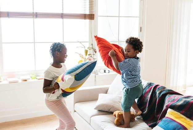 거실에서 싸우는 형제와 자매 베개