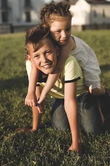 兄と妹は夏に屋外で遊ぶ。クローズアップの肖像画。垂直フレーム
