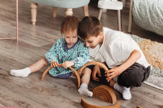 형제와 자매는 어린이 방에서 나무 장난감을 가지고 노는. 아이들은 바닥에서 장난감 디자이너와 놀아요.