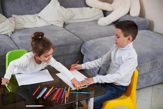 兄と妹は家で遊んだり絵を描いたりします。一緒に時間を過ごす2人の子供。家族の時間。