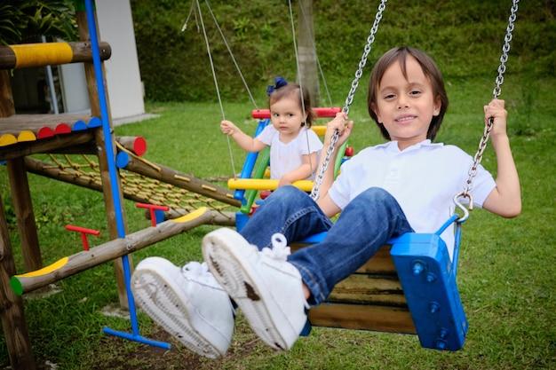 Брат и сестра играют на качелях в парке, улыбаются и веселятся, очень счастливы