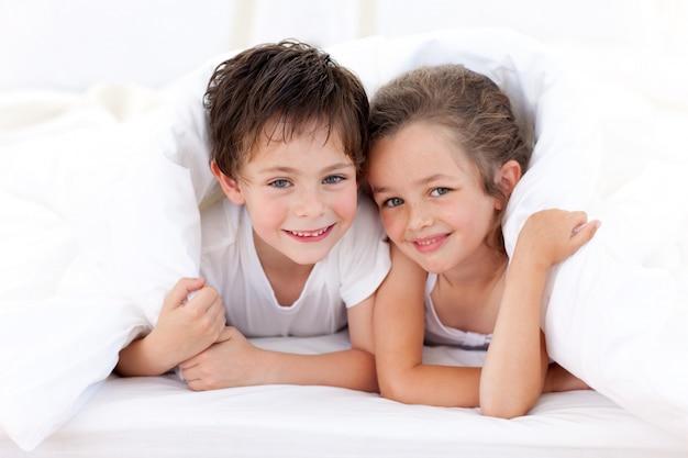親のベッドで遊んでいる兄と妹