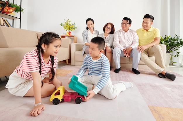 Брат и сестра играют на полу, когда их родители, бабушки и дедушки сидят на диване на заднем плане