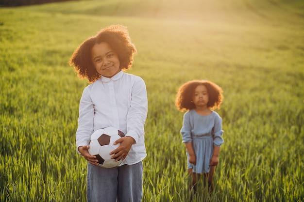 フィールドでボールで遊ぶ兄と妹