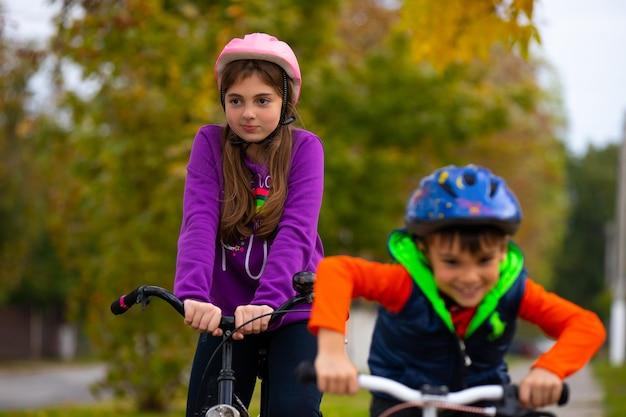 Брат и сестра катаются на велосипедах и в защитных шлемах в осеннем городском парке. на фото деревья сзади размыты.