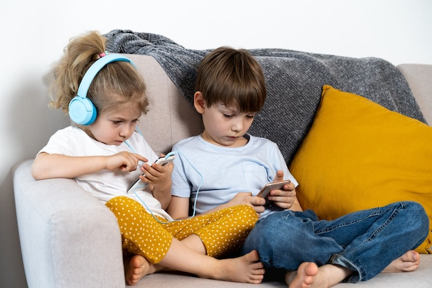 형제 자매는 헤드폰 컨셉의 아이들과 스마트폰 소녀와 함께 소파에 집에 앉아 있습니다.