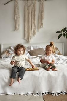 형제 자매는 침대에 앉아 단단한 치즈를 먹습니다.