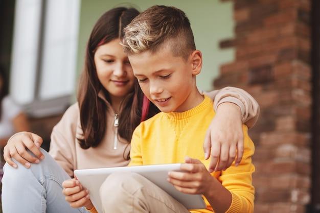 Брат и сестра сидят на ступеньках после школы и играют на цифровом планшете