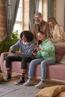 自宅でバックグラウンドで立っている両親と一緒にビデオゲームをしているソファに座っている兄と妹
