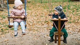 Brother and sister swinging in park