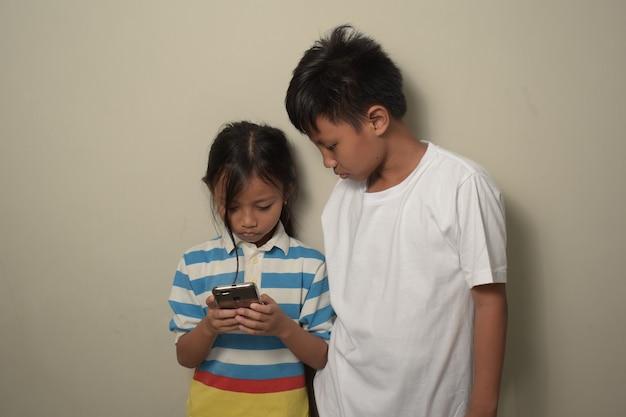 兄と妹はスマートフォンを使用して、電話の画面を見ています