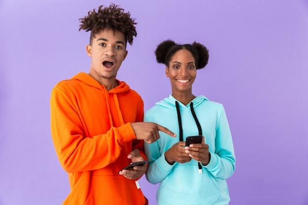 Брат и сестра в ярких свитшотах с помощью мобильных телефонов, изолированные на фиолетовой стене
