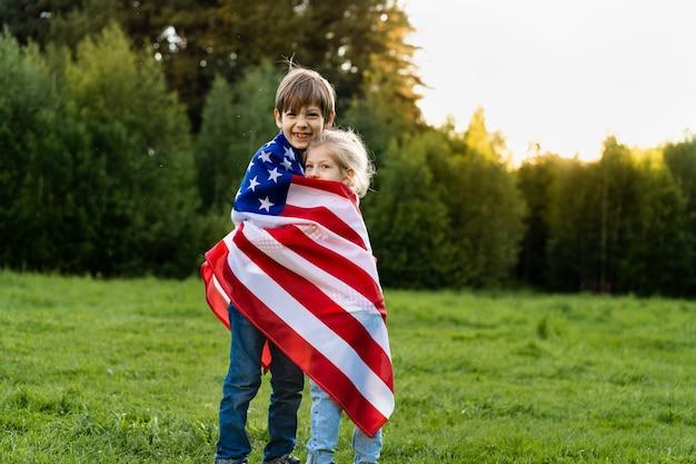 미국 국기를 껴안고 있는 형제 자매, 미국 독립 기념일에 행복한 아이들.