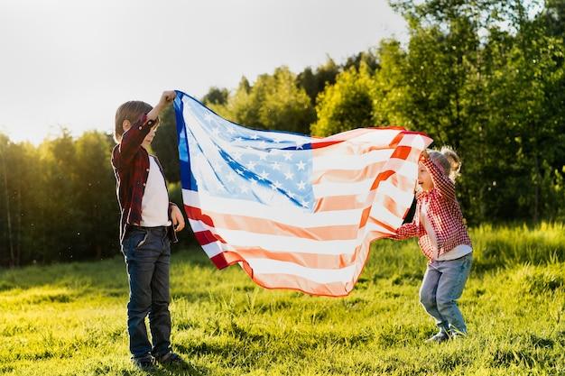 햇빛에 미국 국기를 든 형제 자매, 미국 독립 기념일에 행복한 아이들