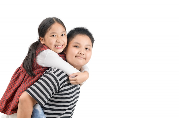 Brother giving piggyback ride to sister isolated on white