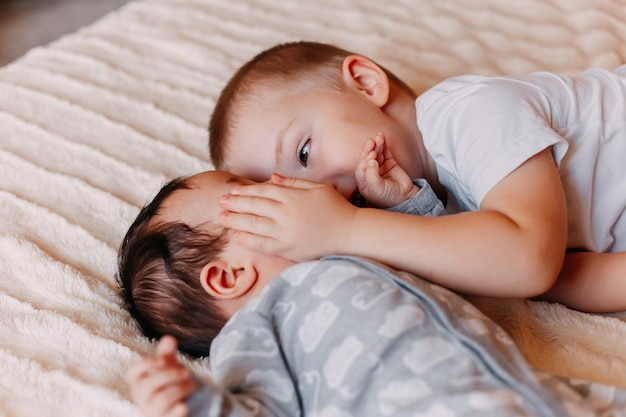 The brother and his cheerful little sister lying on bed girl yawn