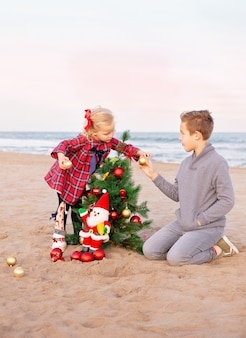Brother and his little sister decorating christmas tree on the beach.