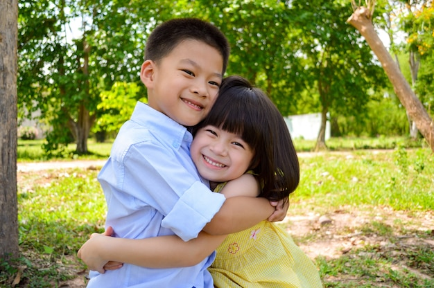 Brother hugging sister. adorable boy and girl hugging each other in summer time.