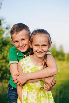 동생이 여동생을 안아줍니다. 작은 친구. 녹색 티셔츠와 녹색 드레스