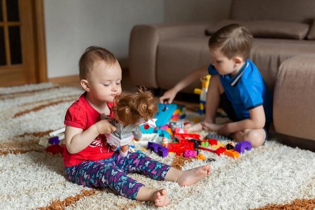 Брат играет с конструктором на ковре, а моя сестра играет в куклу.