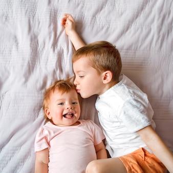 兄は妹にキスして笑う、小さな子供たちの上面図。