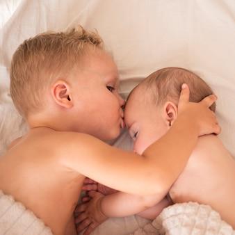 Брат целует новорожденного ребенка в лоб