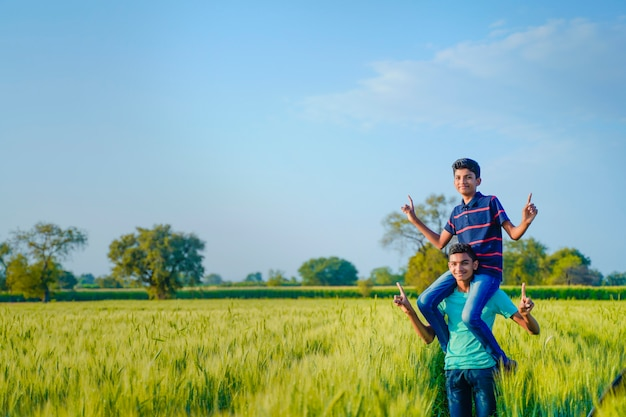 Brother piggyback his little brother in wheat field, rural india