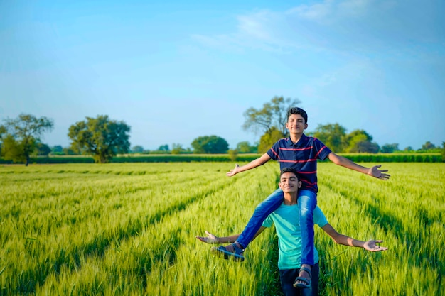 Brother piggyback his little brother in wheat field