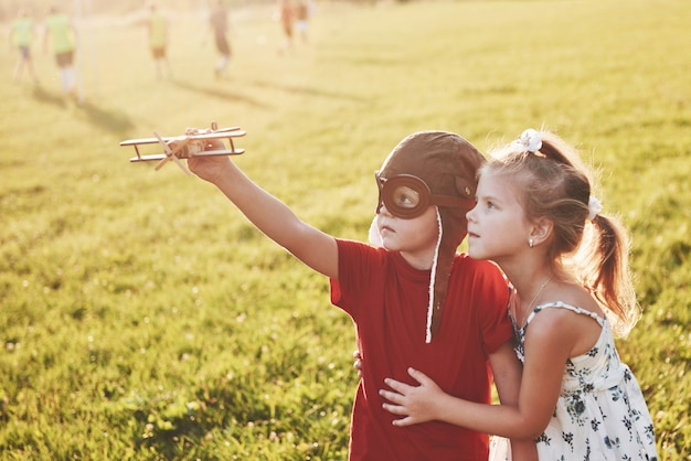 Brother and sister are playing together. two children playing with a wooden airplane outdoor