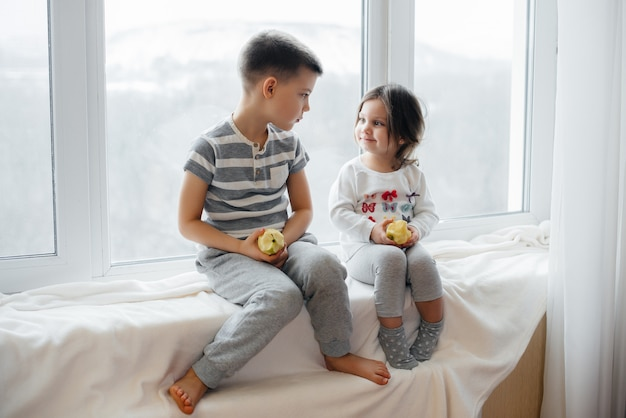 Brother and sister are sitting on the windowsill playing and eating apples. happiness