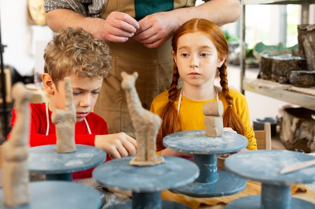 Brother and sister attending art school modeling clay sculptures