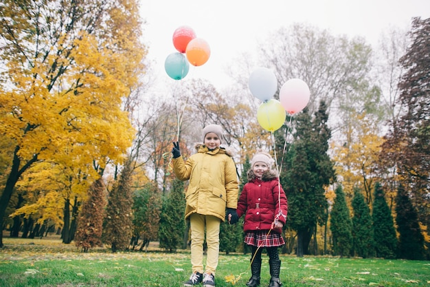 Brother and sister in an autumn park with balloons