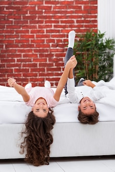 Brother and sister on bed edge with head hanging