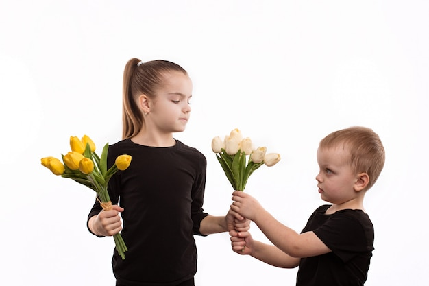 Brother and sister in black blouses holding tulips in their hands.