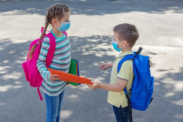 Brother and sister or boy and girl wearing protective medical masks in the schoolyard