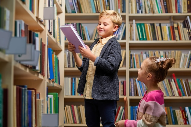 Brother and sister choose books in library, having conversation, in library of school